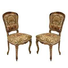 Pair of 18th Century French Louis XV style side chairs, cartouche shaped back and shapely serpentine seat, floral silk upholstery, supported on on front cabriole legs and back legs outswept, carved frame with foliage on crest and seat frieze.