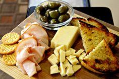 Sartori Extra-Aged Asiago with crackers, garlic stuffed green olives, turkey and crusty artisan bread