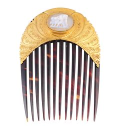 A Victorian tortoiseshell hair comb, circa 1870, the thirteen tortoiseshell prongs set to the top with a curved plaque of textured metal with delicate scroll and beaded detailing, set to the centre with an oval raised mount set with a carved cameo of an angel and two lions, within subtle scroll detailing. In fitted case. Stamped PEIRCE to the reverse. Length approx 11cm. Width approximately 7.5cm.