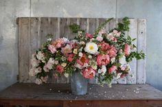 arrangement of 'Coral Charm' peonies, rose 'Ghislaine de Feligonde' and 'Dupontii', apples, sweet peas, foxglove, wild roses and ninebark foliage from Floret Flower Farm