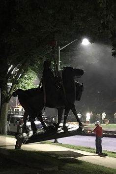 """Workers load statues of Confederate generals Robert E. Lee and Thomas """"Stonewall"""" Jackson on a flatbed truck in the early hours of August 16, 2017 in Baltimore, Maryland. Photo credit should read Alec MacGillis/AFP/Getty Images."""