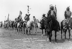 Procession of men of the Blackfoot Confederacy on horseback 1910.