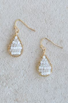 Looking for versatile earrings that will go with just about anything? These white beaded teardrop earrings are sure to be your go-to! Featuring a j-shaped hook and gold wire wrapped framework, there's