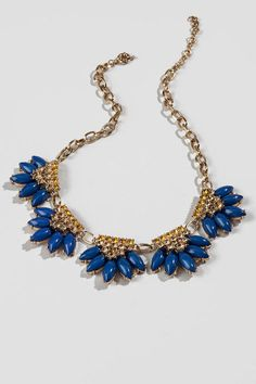 """Add some color & shine to your look with the Cibola Statement Necklace. Gold crystals accent deep navy stone clusters that lay in a linear pattern on a shiny gold chain. Wear with a sweater wrap and tall boots for a classy daytime look.<br />%0D%0A<br />%0D%0A- Finished with a circle spring clasp<br />%0D%0A- 18"""" length<br />%0D%0A- 2.5"""" extension<br />%0D%0A- Lead & nickel free<br />%0D%0A- Imported"""