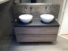 (Welbie Sanitair) Badkamer Millingen aan de Rijn. Eindresultaat. Strak meubel met veel opbergruimte, maar door de opbouw waskommen en kiezels op achterwand toch een warme uitstraling. Meer informatie voor eigen badkamer ontwerp op www.welbie.nl