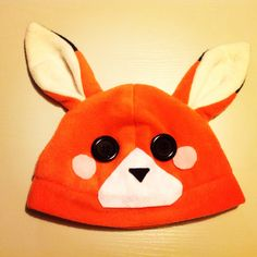 A fox beanie/plushy hat! It's made out of soft, kind of stretchy polar fleece! The blush marks, muzzle, and nose are made out of felt, and is securely hot glued on. The eyes are black buttons, and are also securely affixed with hot glue.    The hat would fit on a head with an approx. circumferenc...