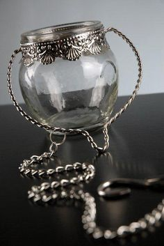 7.00 SALE PRICE! With an ornate metal collar and a simple, glass body, this piece will perfectly display tealights, vase gems, or single flower blossoms. The...