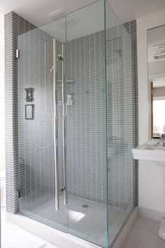 """Less is more. Small space bathrooms are best kept wide open with modern floor-to-ceiling shower stalls and glass partitions. A tub or shower floor and curtains would have cluttered up this space instantly."""