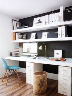 Escritorio completamente incorporado al muro, con una mesa y cajoneras en blanco y repisas blancas sobre muro negro. La silla es una Eames de respaldo calipso y patas de madera, a un costado un trozo de tronco que sirve de piso.