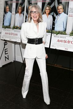 Diane Keaton in a white pantsuit with a black statement belt