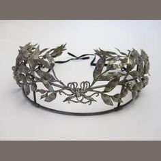 An early 20th century tiara  Formed as trailing laurel leaves with berries, all tied with a ribbon bow to the front, fabric ribbon ties to back,