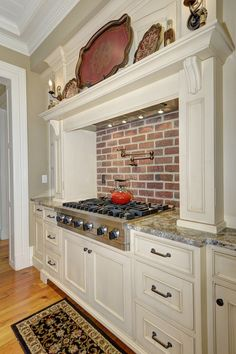 White cabinets, brick wall, gas stove, red accent