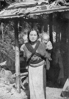 Historical tandem wearing photo: A Japanese mother in 1917 babywearing two from National Geographic.