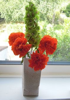 A bright display of crepe paper marigolds and bells of Ireland in a plain cardboard vase for a neutral room