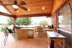 Outdoor kitchen with stainless BBQ, refrigerator, drawer and cabinet space. Natural stone countertops and granite bar table. By Outdoor Signature in Argyle, TX