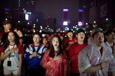 South Korean football fans sing their national anthem as they watch their team play against Algeria in the 2014 World Cup in Brazil, on giant screens in central Seoul on June 23, 2014. Algeria moved them tantalizingly close to a first ever appearance in the knock-out rounds after dishing out a 4-2 defeat to South Korea in Porto Alegre.