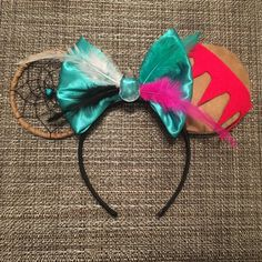 These Pocahontas Disney ears bring a natural native feel foe the movie. It includes feathers to match her friends the hummingbird and raccoon. The clear stone in the middle for the stone she wears around her neck. This does come in 2 options with the ears to be one side dreamcatcher and the other to match her dress and arm tattoo and the other has both ears dreamcatchers.