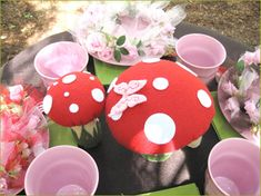pink plates, green napkins, brown tablecloth, toadstools, flowers, butterflies