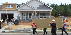 """Hard at work attaching •Restoration Classic® Double 4"""" clapboard siding, charcoal gray"""