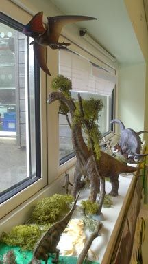 "A dinosaur scene created in a classroom, a flying reptile suspended from the ceiling by a thin thread surveys a prehistoric diorama made by a clever teacher utilising the ""dead space"" of a windowsill in his classroom."