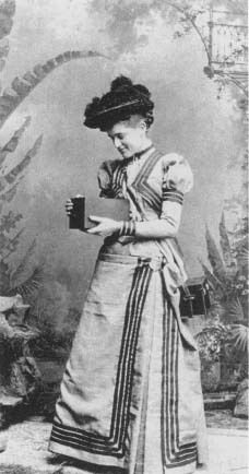"Kitty Kramer, the first Kodak Girl, shown using a Kodak camera in 1890.   Reproduced by permission of AP/Wide World Photos. ""In the mid-1880s Eastman had told J. Walther Thompson that ""a picture of a pretty girl sells more than a tree or a house"" in magazine advertisements.  Eastman's ideas was a girl in a striped dress, fashionably holding a camera, and thus the Kodak girl was born."