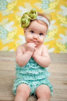 fillette avec barboteuse en dentelle turquoise et bandeau à fleur verte