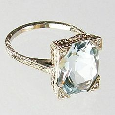 Aqua is untreated, in 18k white gold. 5.05tcw for aqua, plus 4 melee diamonds, ca 1920's