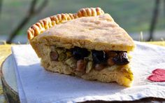 <p>In this pie, its distinct taste is balanced by salty capers, savory black olives, and sweet raisins cooked with aromatic chopped onion.</p>
