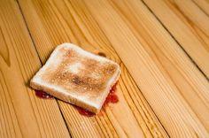 Slice of toast with strawberry jam upside down on floor