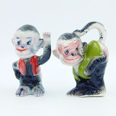 Set of vintage pre-owned gloss glazed porcelain ceramic figural novelty salt and pepper shakers set.  A pair of black and white smiling mischievous monkeys with pink faces and open eyes with long eye lashes.  One monkey is wearing a green vest and is bent over at the waist with one hand on his pink bottom and his tail curled up to his head.  The other monkey is wearing a red vest and appears to be waving with one hand  #Vintage #SaltAndPepperShakers #Monkey