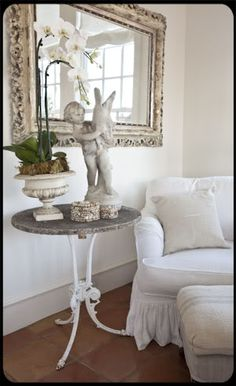Love the statue and the urn filled with white orchids..my fav flower for home decor...simple elegance!
