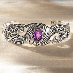 Balinese silversmith Wayan Sarjana comes from a family of craftsmen, and after years of apprenticeship, now runs his own home workshop near the craft market of his island village. Sarjana elaborates on ancient Indonesian designs to evoke a historical and mystical mood in his jeweled creation. Floral scrolls frame a faceted amethyst center in this exquisite sterling silver bracelet.