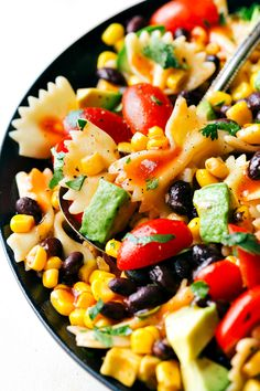 A delicious and super simple Tex Mex Pasta Salad with corn, black beans, cherry tomatoes, and avocados. An easy Catalina dressing tops this salad. Recipe from chelseasmessyapron.com