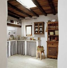 Rustic kitchen with curtained cabinets. Photo by Jordi Canosa.