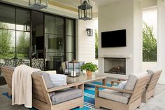 Chic covered patio with beadboard ceiling accented with two gray carriage lanterns illuminating a teak sofa lined with gray cushions as well as a teak accent chair facing a teak coffee table with stone top placed atop a cerulean blue striped outdoor rug facing a white brick fireplace lined with a slat panel tv.