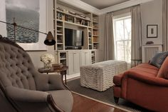 A burnt orange sofa compellingly breaks up the soft gray-blue palette of this transitional living room. A large ottoman doubles as a coffee table and extra seating for larger gatherings.
