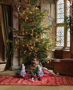 In the banquet hall of Haddon Hall, a 12th—century manor in Derbyshire, England, the twin sons of Edward and Gabrielle Manners, Alfred and Vesey, play under a Christmas tree from the estate decorated with pinecones, dried oranges, and cinnamon sticks; the walls were made from local limestone and gritrock, the oak coffer is early 17th century, and the antique rug is Moroccan.