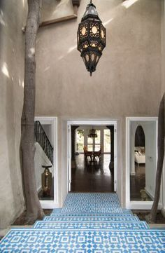 cp: Granada Tile's Fez design in West Hollywood.  Not only do the geometric blue and white tiles really draw you in and welcome you to the front door but the combination of the natural textured walls, the trees given space each side and the hanging Moroccan lamp complete the picture with finesse.