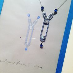 Art Deco style white gold, sapphire and diamond pendant pictures next to the original working drawing in gouache.