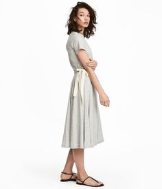 Gray melange. Calf-length dress in melange cotton jersey with short sleeves. Elasticized seam, drawstring, and side ties at waist. Flared skirt. Unlined.