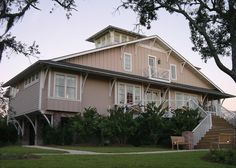 I love the outside of this house. It's a fusion of coastal style and farmhouse architecture. The home is on stilts to keep it above flood level. A second-story balcony and upper watchtower have views of the beach.