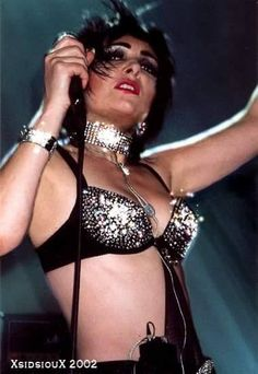 A photo of Siouxsie wearing a glittery bra and a neck collar. <3