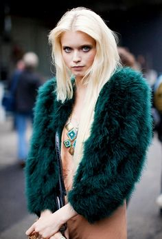 Abbey Lee Kershaw wears a gold and turquoise statement necklace with a nude dress and green fur coat