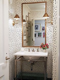 Wallpaper and brass details in this powder room