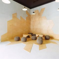 seat area on the corner of meeting room, equipped with several knitted stools, two low tables and black pendant lamps
