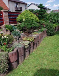 V přední, níže položené části zahrady je pomocí betonových tvarovek vybudována terasa, díky níž jsou záhony v úrovni chodníku.