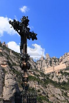 Beautiful cross sculpture with Montserrat mountain and monastery on background, a very important tourist and pilgrim destination (Catalonia, Spain).