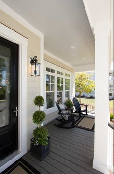 Light color siding, small porch and wide door and window trim.