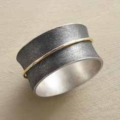 """SPUN INTO GOLD RING -- Like a wisp of straw spun into gold, a 14kt ring spins on its base band of etched, oxidized sterling silver. A handmade 14kt gold band spinner ring in whole sizes 5 to 9. 7/16""""W. This ring is licensed under U.S. patent nos. 6,497,117 and 6,395,732."""