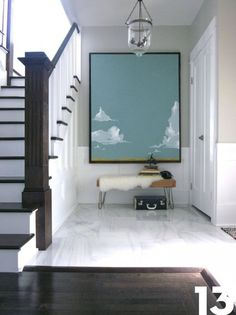 entry with oversize art. white marble floors